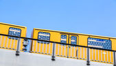 Yellow berlin subway moving on a bridge isolated on blue sky — Stock Photo