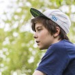 Profile of a young boy with basecap and blurred green leafs in b — Stock Photo