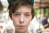 Young boy with basecap looking into the camera, blurred people i — Stock Photo