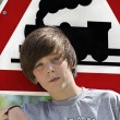 Portrait of a cool boy in front of an locomotive traffic sign — Stock Photo
