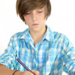 School boy working with a pencil, isolated on white — Stock Photo