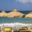 Stock Photo: Three orange, old parasols and sunlounger with blue ocein ba