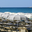 Stock Photo: Groupe of parasols and sunlounger with blue ocein backgroun