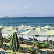 Stock Photo: Groupe of green parasols and sunlounger with blue ocein bac