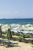 A groupe of green parasols and sunlounger with blue ocean in bac — Stock Photo