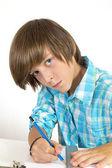 Menino de escola com lápis e régua, isolado no branco — Foto Stock