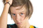 Serious teen boy, one hand in his hair, isolated on white — Stock Photo