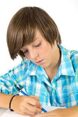 School boy with pencil works concentrated, isolated on white — Stock Photo