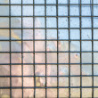 Stock Photo: Metal grid with mirroring surface in background