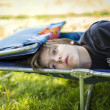 Stock Photo: Dreaming teen boy laying on sunlounger