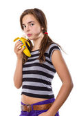 Teenage girl eating a banana, isolated on white — Stock Photo