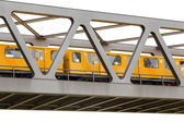 Yellow moving train on an iron bridge with blue sky, isolated on — Stock Photo