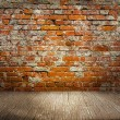Indoor background with red brick wall an wooden plank floor — Stock Photo