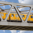 Yellow moving train on an iron bridge with blue sky  — Stock Photo
