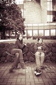 Vintage style portrait of two teenager sitting on iron chairs — Foto de Stock