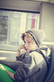 Portrait of a teenager boy with toque, sitting in a bus — Stock Photo