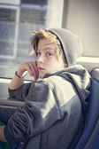 Portrait of a teenager boy with toque, sitting in a bus — Photo