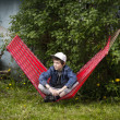 Stock Photo: Cool teenager boy having break in hammock