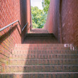A tunnel like stairway with red bricks and handrail — Stock Photo