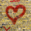 Stock Photo: I love you heart graffiti on a yellow brick wall