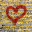 Stock Photo: Heart graffiti on a yellow brick wall background