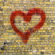 Heart graffiti on a yellow brick wall background — Stock Photo #38653783