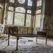 Old rusty bed in ruinous house in front of some windows — Stock Photo