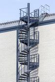 Dark blue circular staircase on a white brick wall — Stock Photo