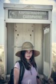 Female teenager with straw hat in an old call box — Stock Photo