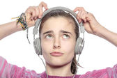 Beautiful teenager girl fumble on her headphones, isolated on wh — Stock Photo
