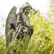 Angel sculpture between blurred spring foliage — Stock Photo #45596305