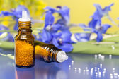 Two bottles with homeopathy globules and flowers, with blue refl — Stock Photo