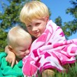 Постер, плакат: Big Brother and Baby Hugging in Beach Towels
