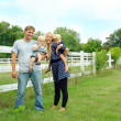 Happy Family Outside by White Fence — Stock Photo #31657867