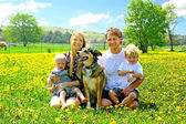 Happy Family Sitting In Dandelion Field — Stock Photo