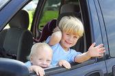 Children Smiling Out Van Window — Stock Photo