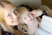 Frau mit baby auf ihrem schoß lesen — Stockfoto