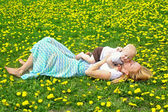 Mother Kissing Baby in Dandelion Field — Stock Photo