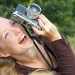 Stock Photo: Happy Woman Taking Pictures with Vintage Camera