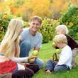 Family Eating Apples at Orchard in Autumn — Stock Photo