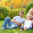 Happy Family Sitting in the Grass Eating Apples at Orchard — Stock Photo