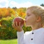 Child Kissing Apple on Autumn Day — Stock Photo