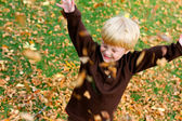 Happy Young Child Playing Outside in The Fallen Leaves — Stock Photo
