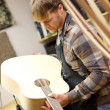 Luthier Inspecting Handmade Guitar in Workshop — Stock Photo