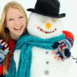 Happy Woman Hugging Snowman Outside in Winter — Stock Photo