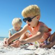 Stock Photo: Two Children Playing in the Sand at the Beach