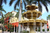 Water Fountain in Front of Colorful Building and Palm Trees — Stock Photo