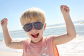 Young Child Flexing Muscles on Beach — Stock Photo