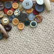 Variety of Vintage Buttons Scattered on Knit Fabric Background — Stock Photo