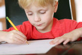 Young Child Focusing on Work as he Writes with Pencil — Stock Photo